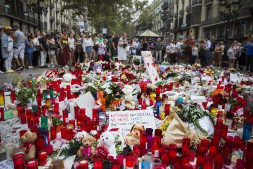 Turista y barceloneses frente a un altar improvisado en Las Ramblas de Barcelona, en homenaje a las víctimas del atentado. Autor: Massimiliano Minocri para El País