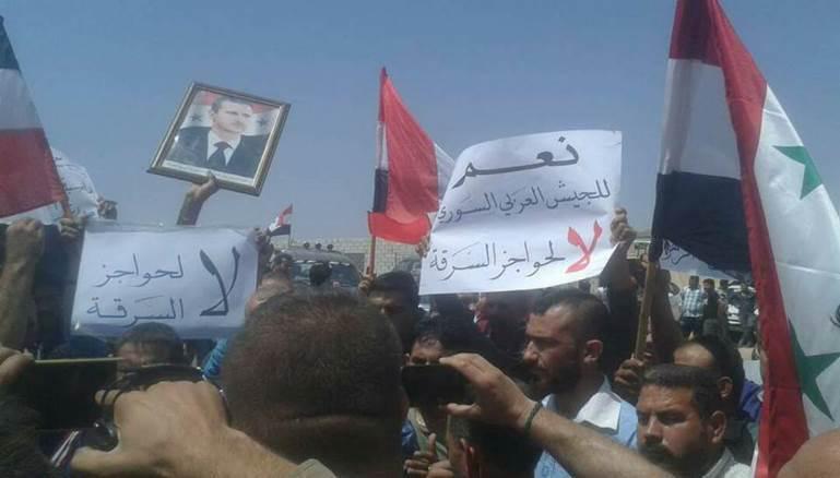 Manifestantes partidarios de Asad acusan a las milicias progubernamentales de extorsionar a los civiles en los puestos militares de control. Alepo, 7/07/2017. (Foto: Al Modon)