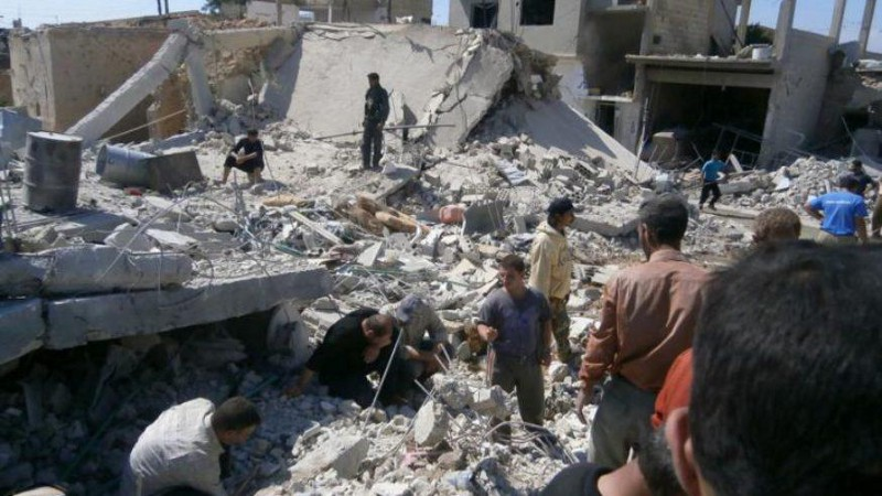 Un folleto publicado por la agencia de noticias Shaam News Network, de la oposición siria, muestra a unos sirios buscando supervivientes entre los escombros en la ciudad de Qusayr, en la provincia de Homs, el 21 de mayo de 2013. (Foto: AFP - HO)